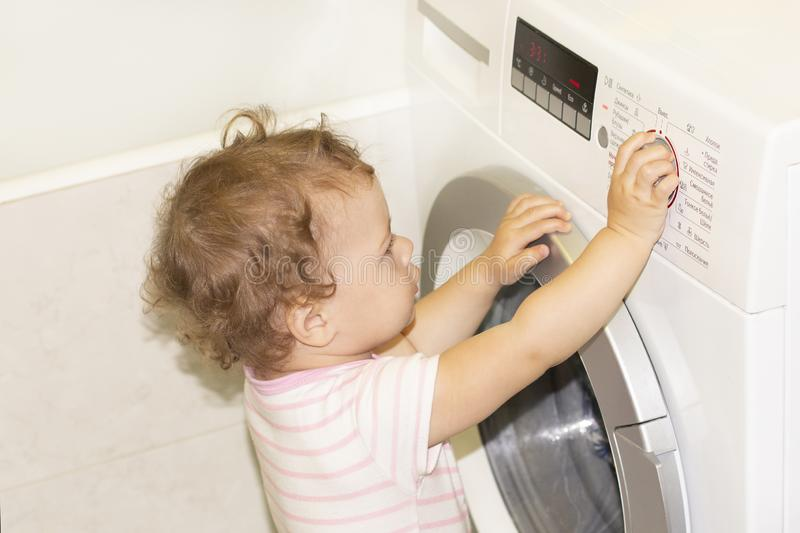 一点女婴按在洗衣机的按钮 免版税库存图片