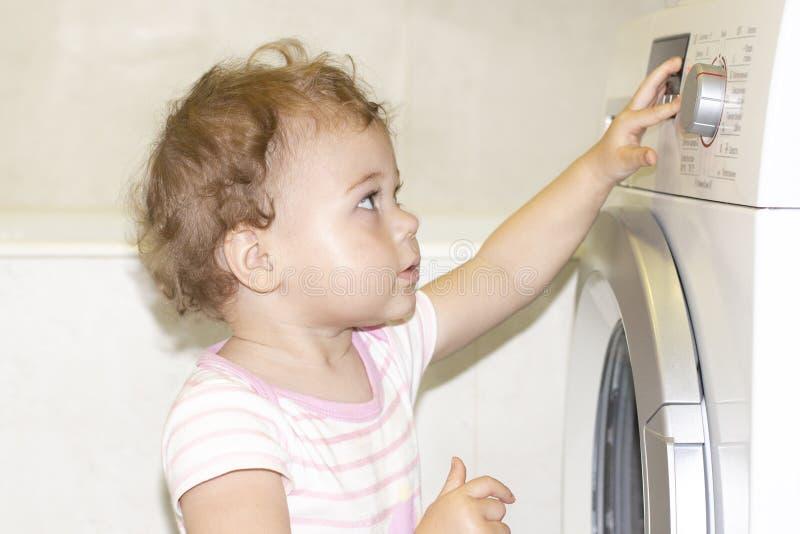 一点女婴按在洗衣机的按钮 欧洲白种人孩子和洗衣机 免版税图库摄影
