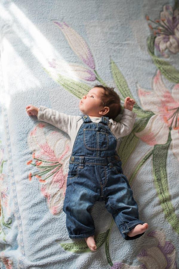 一点婴孩在床上说谎 说谎在床,顶视图上的逗人喜爱的矮小的婴孩 免版税库存图片