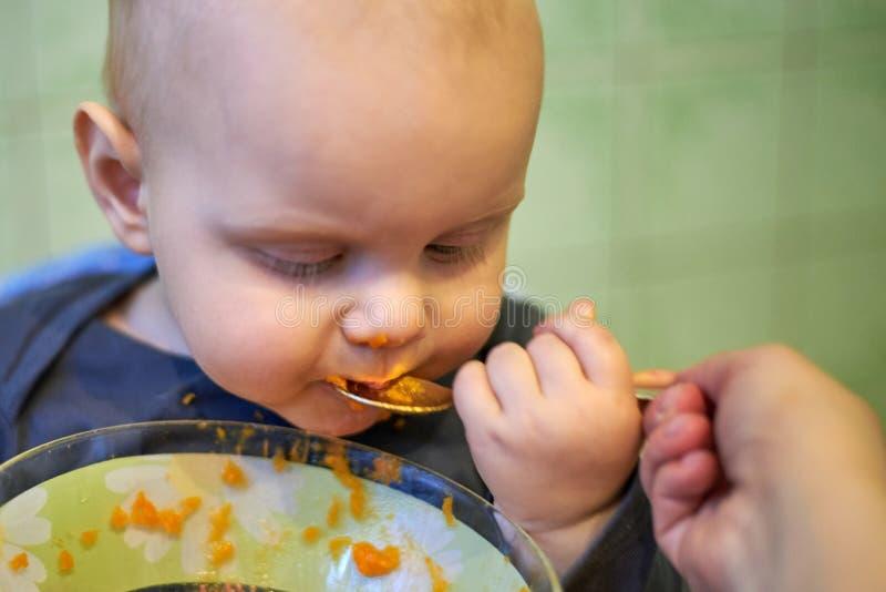 一点婴孩学会单独吃与匙子 免版税库存图片