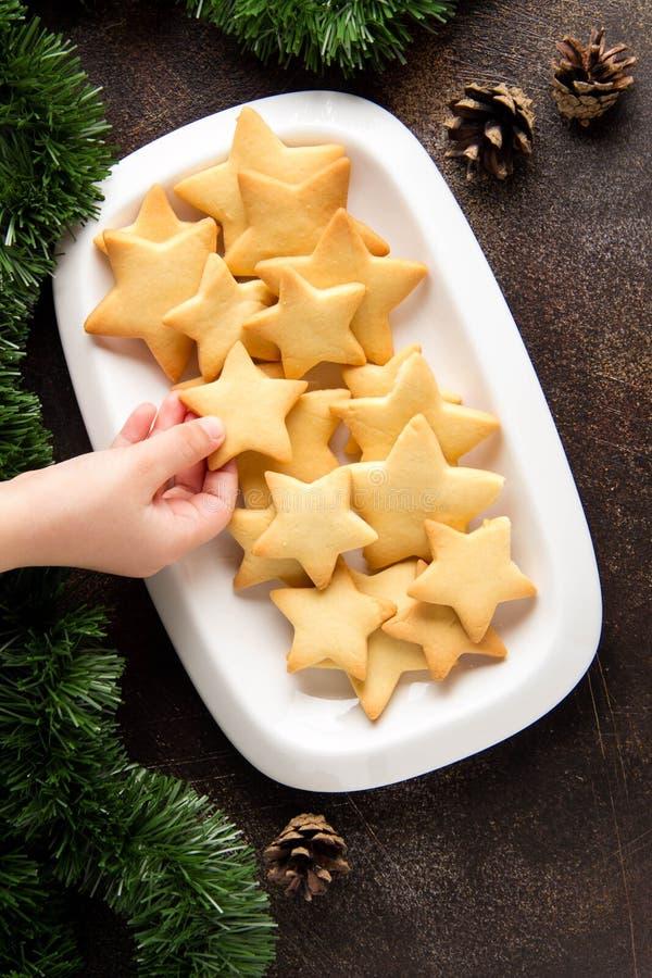 一点婴孩手采取从板材,孩子的,食物假日甜圣诞节快餐的星曲奇饼 库存图片