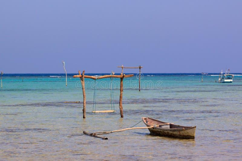 一点小船和swining的杆在原始海岸中Karimunjawa,Java,印度尼西亚的水 库存照片