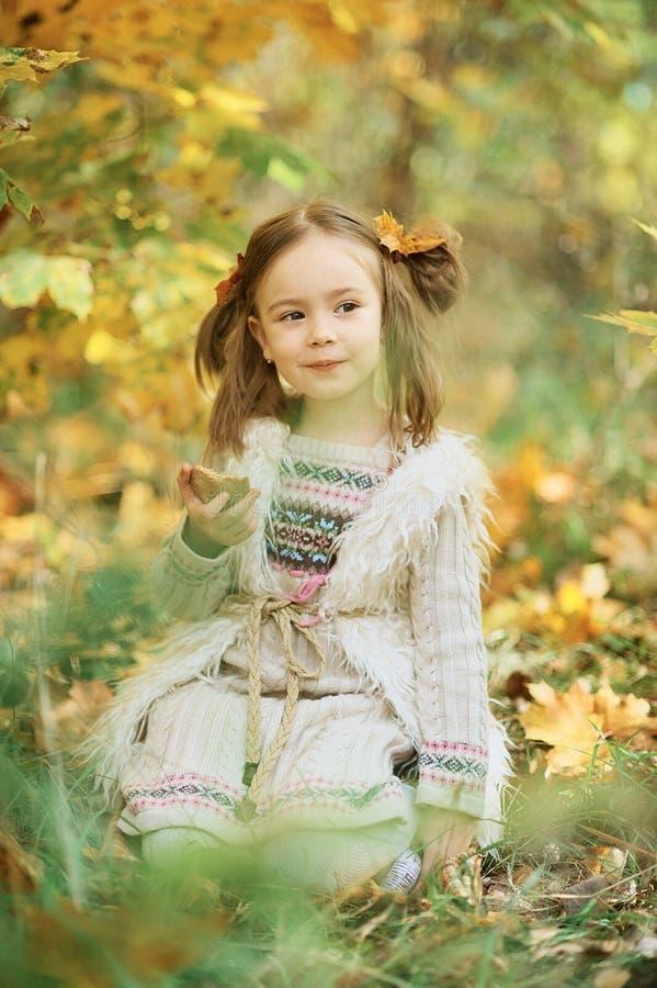 一点微笑的女孩坐格子花呢披肩在秋天公园 逗人喜爱的白种人女孩在手中拿着黄色枫叶的秋天公园 免版税库存照片