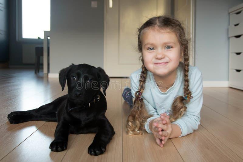 一点微笑的婴孩孩子和小狗拉布拉多猎犬 免版税库存照片