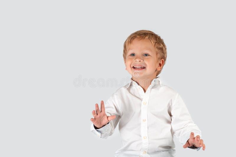一点微笑的男孩佩带的白色shir的半身画象 免版税库存图片