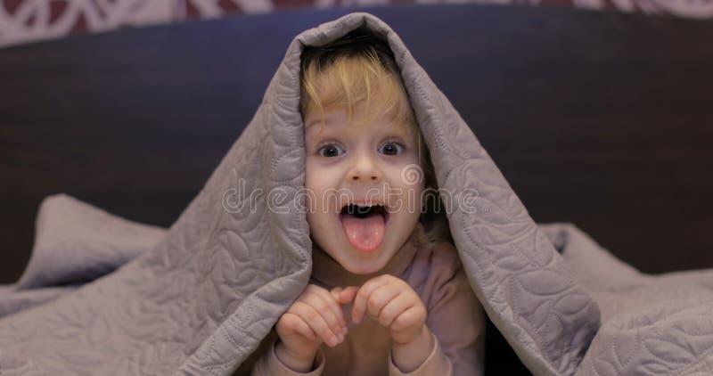 一点快乐的女孩掩藏在毯子和看着电视下 孩子睡眠的概念 库存图片
