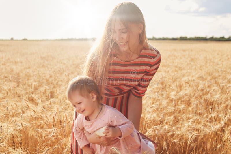 一点快乐的孩子获得与她的母亲的乐趣,拿着面包在手,享受她的童年 拿着她的愉快的嬉戏的妈妈 免版税图库摄影