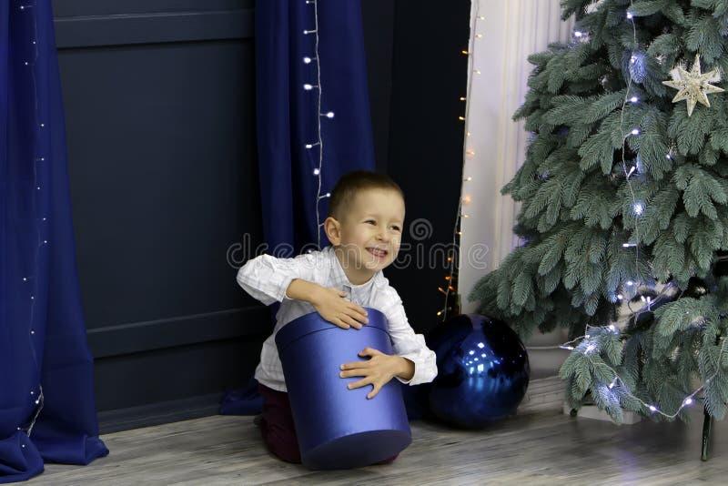 一点愉快的男孩坐地板在圣诞树附近并且打开一件美丽的礼物 免版税图库摄影