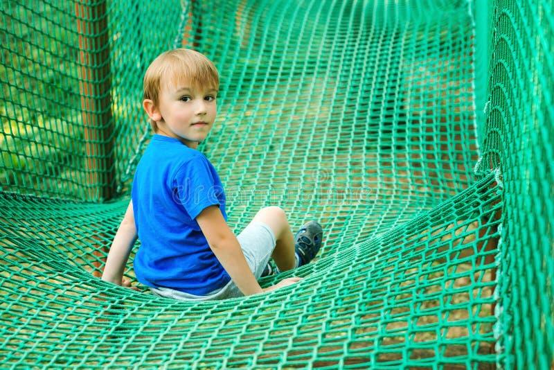 一点愉快的男孩获得乐趣在冒险公园 使用在户外操场的孩子 E 夏天休假 孩子戏剧 库存照片