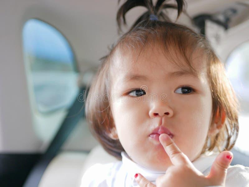 一点把她的手指放的亚裔女婴在她的认为某事的嘴唇上 免版税库存照片