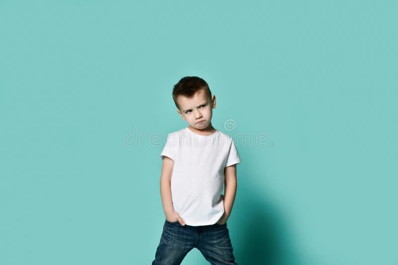 一点摆在蓝色墙壁前面的时兴的男孩 免版税库存图片