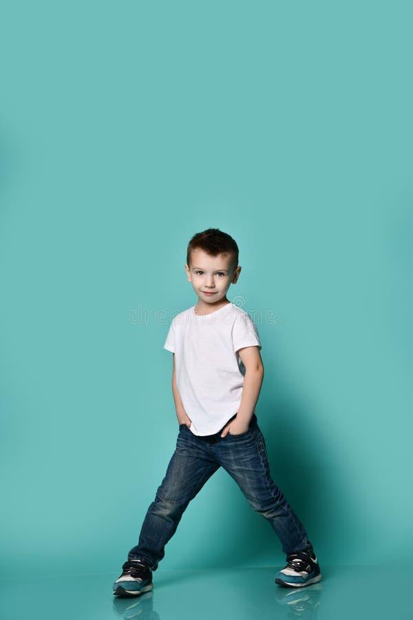 一点摆在蓝色墙壁前面的时兴的男孩 库存图片