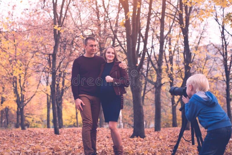 一点有一台大SLR照相机的白肤金发的男孩在三脚架 照片一对已婚夫妇,怀孕 全家福会议 免版税库存图片