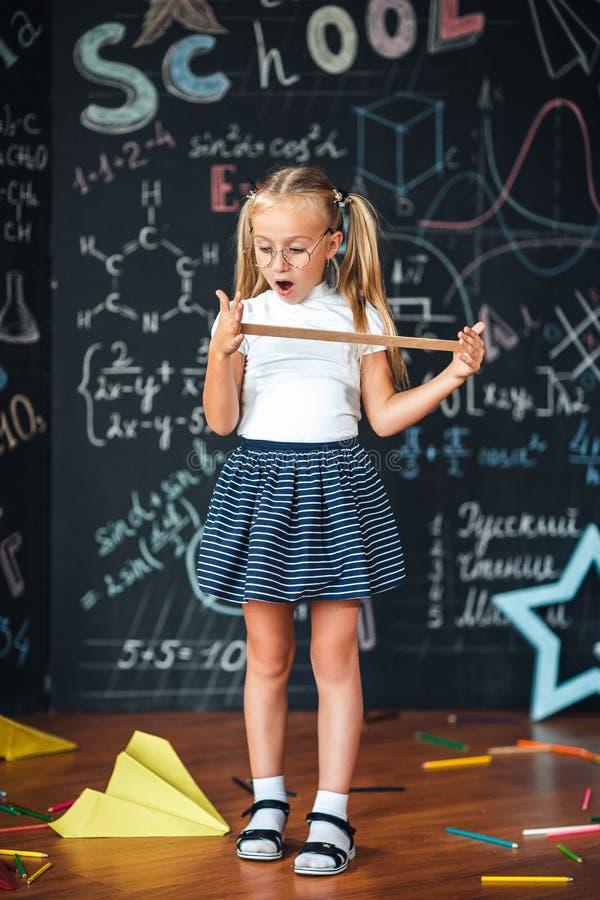 一点有一张惊奇的面孔的白肤金发的女孩与在她的手学生女孩的一个统治者有反对黑板的大统治者的有学校的 免版税库存照片