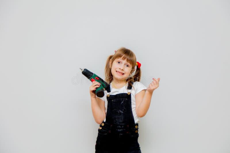 一点有一把螺丝刀的惊奇的女孩在修理期间 免版税库存照片
