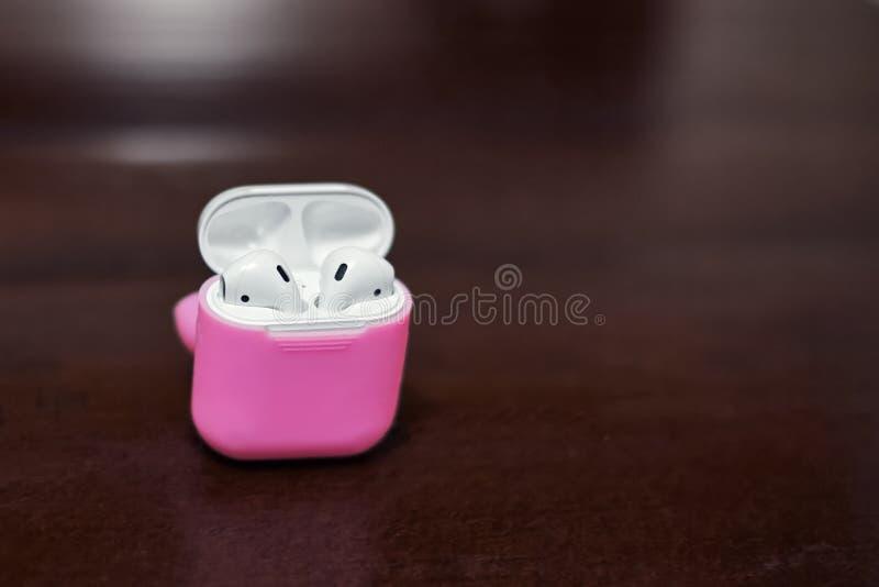 一点有充电器箱子的白色无线耳机在明亮的桃红色盖子箱子 免版税库存照片