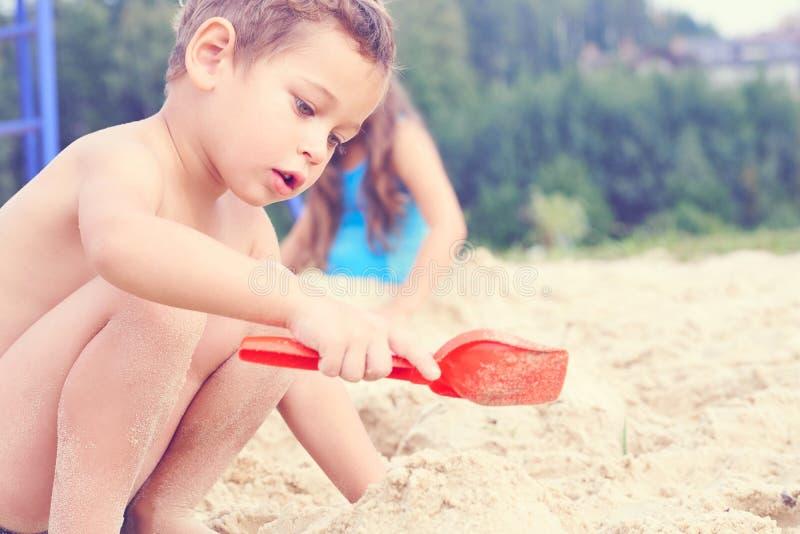 一点有塑料小铲的逗人喜爱的男孩在手中做沙子城堡在海滩 免版税库存照片