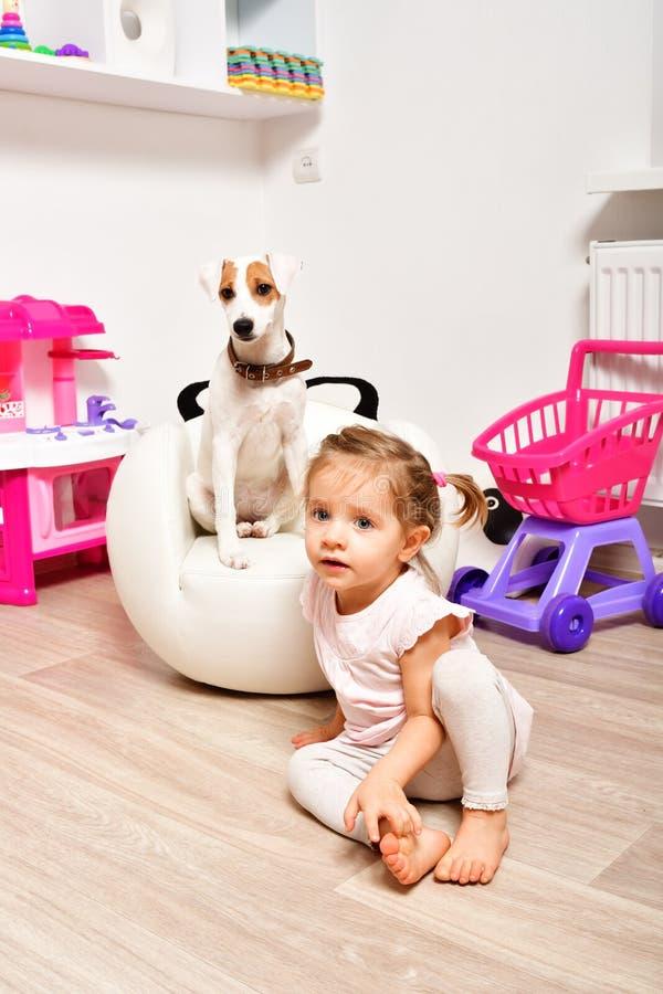 一点有她的狗的逗人喜爱的女孩 免版税库存图片