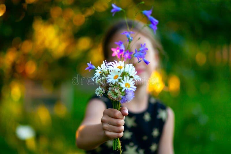 一点有野花花束的逗人喜爱的女孩  孩子给花妈妈 在手上的接近的看法有礼物的 库存图片