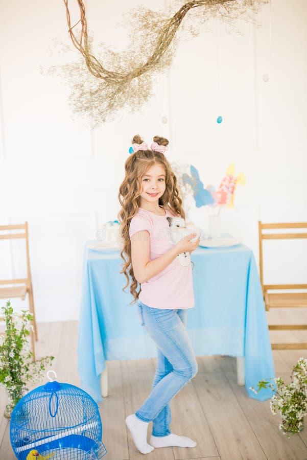一点有长的卷发有小的兔宝宝的和复活节装饰的逗人喜爱的女孩在家在桌上 免版税库存照片