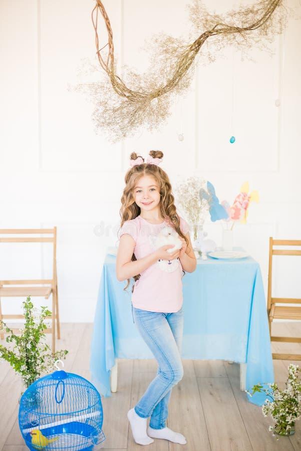 一点有长的卷发有小的兔宝宝的和复活节装饰的逗人喜爱的女孩在家在桌上 免版税库存图片