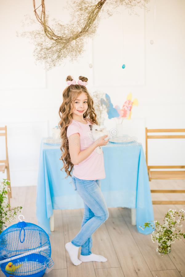 一点有长的卷发有小的兔宝宝的和复活节装饰的逗人喜爱的女孩在家在桌上 库存照片