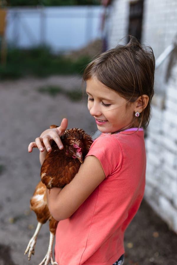 一点有鸡的农村女孩在她的胳膊 库存照片