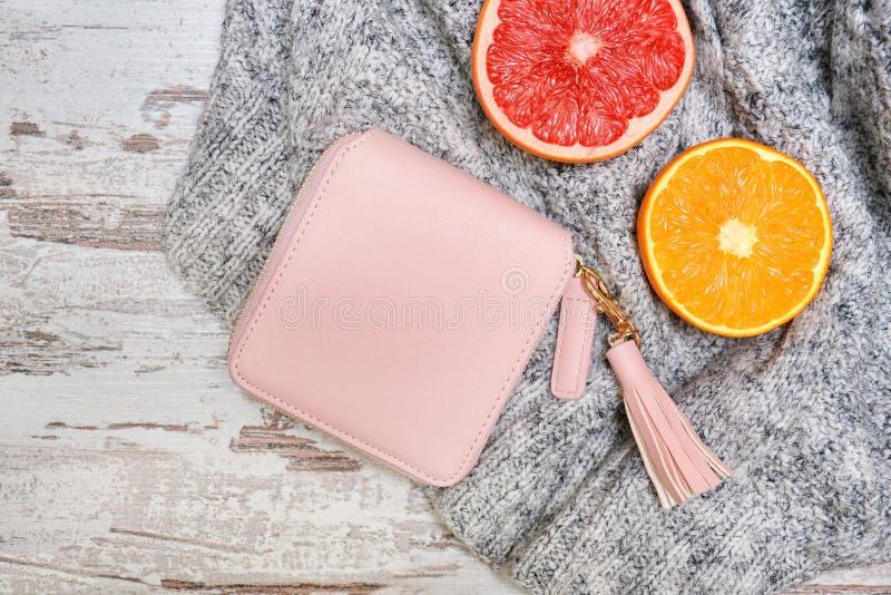 一点桃红色女性钱包和柑橘在毛线衣 时兴的c 免版税库存图片