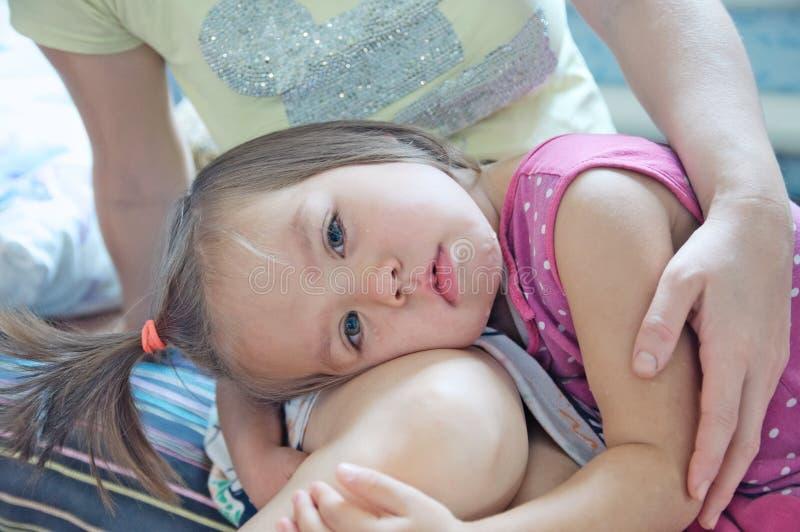 一点母亲膝盖的哀伤的女孩 母亲藏品哭泣的女孩 使小孩镇静下来 啜泣的泪花 免版税库存图片