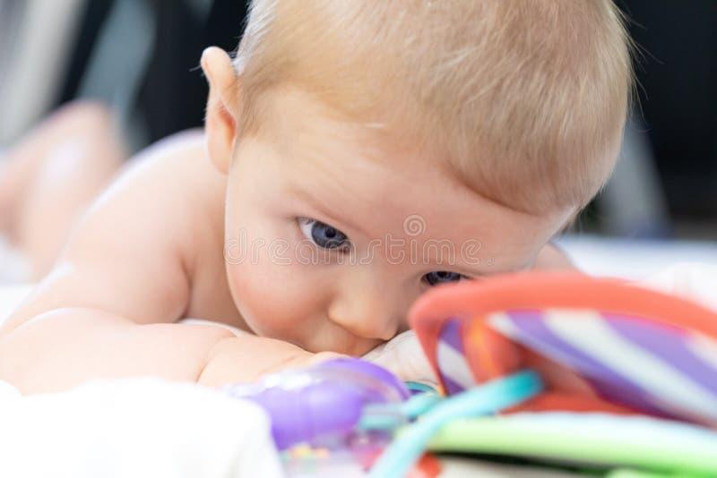 一点注视它五颜六色的玩具的新生儿 图库摄影