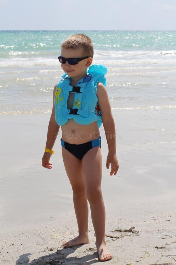 一点海滩的逗人喜爱的男孩在救生衣 库存照片