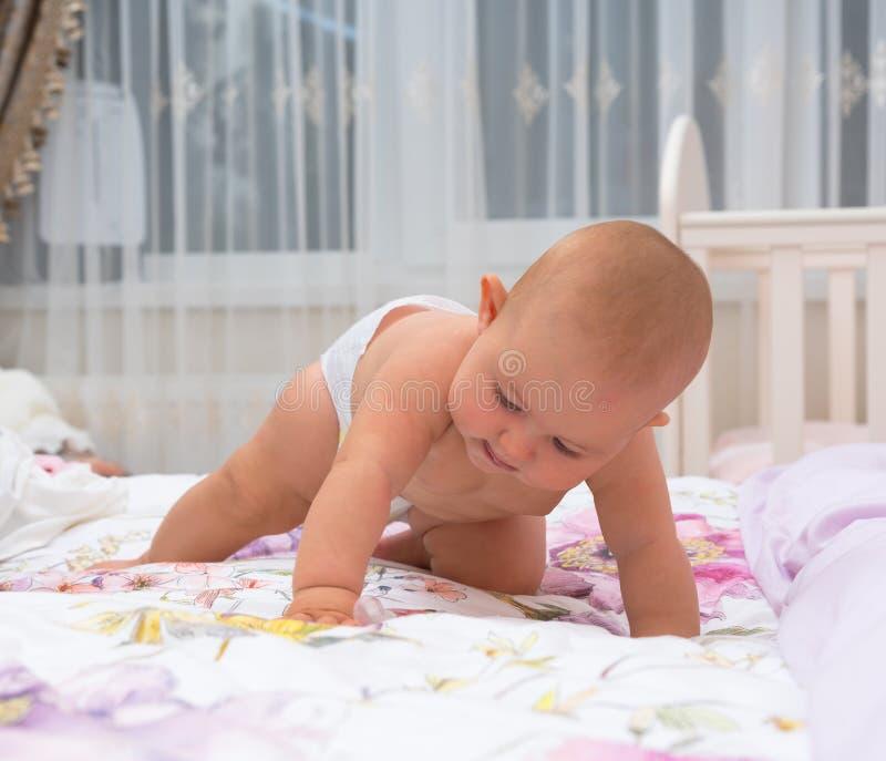 一点爬行在床上的尿布的女婴 免版税图库摄影