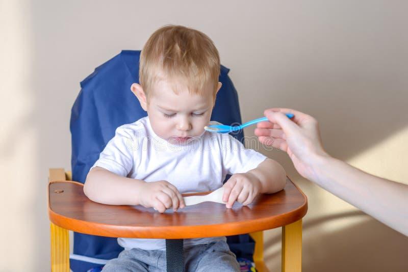 一点男婴在厨房里学会吃在儿童的桌上 妈妈哺养提供粥匙子  库存照片