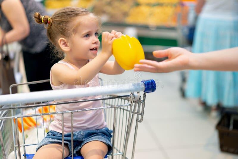 一点白种人女孩在超级市场选择新鲜蔬菜 免版税库存图片
