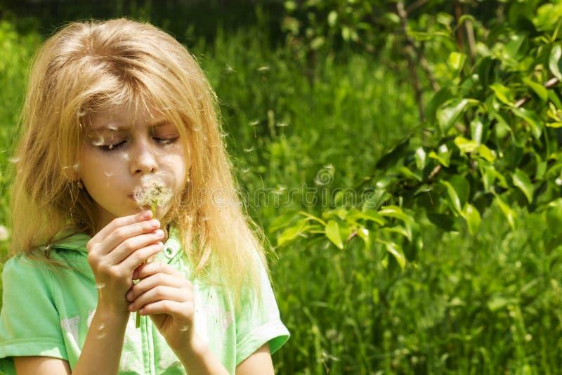 一点白肤金发的女孩吹的蒲公英 免版税库存照片