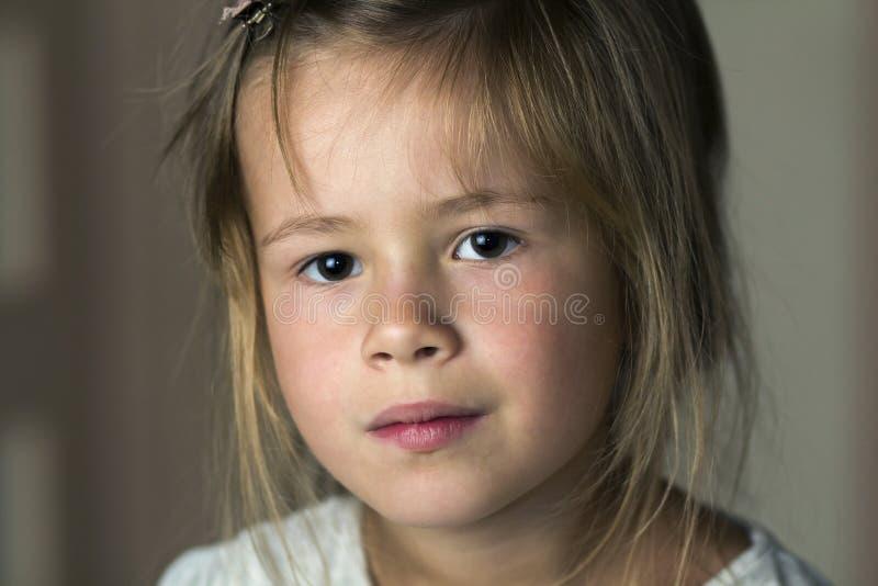 一点的画象有灰色的逗人喜爱的相当幼儿女孩注视a 免版税库存照片