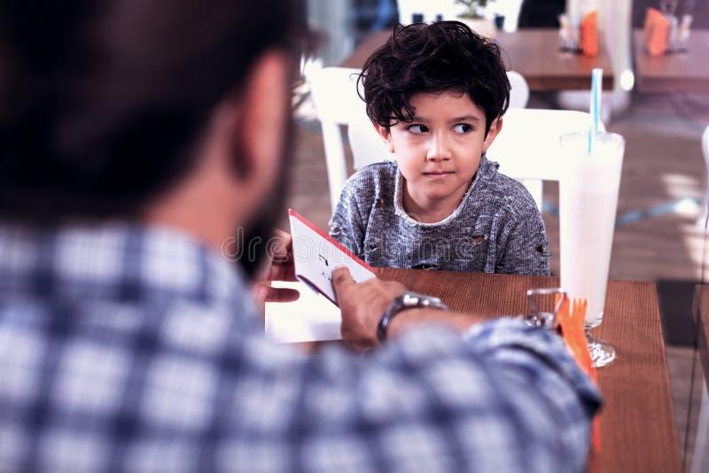 一点穿时髦的毛线衣的逗人喜爱的深色头发的男孩听他的家庭教师 库存图片