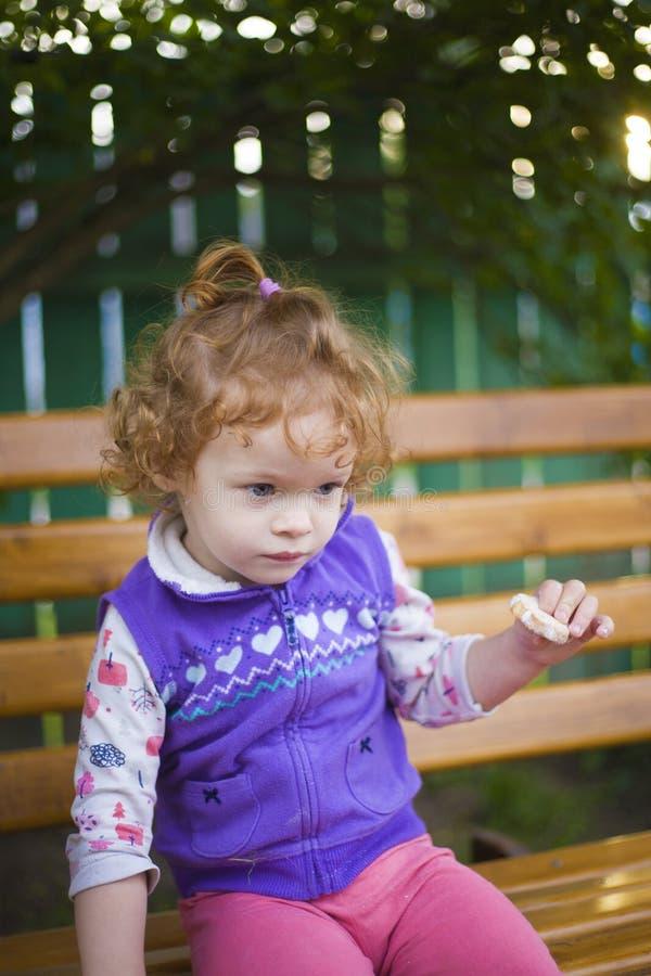 一点红头发人女孩坐长凳 库存照片