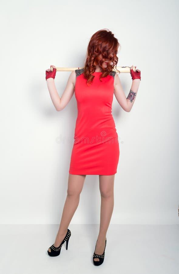 一点红色礼服和红色皮手套的典雅的年轻红头发人妇女,挥舞棒球棒 免版税库存图片