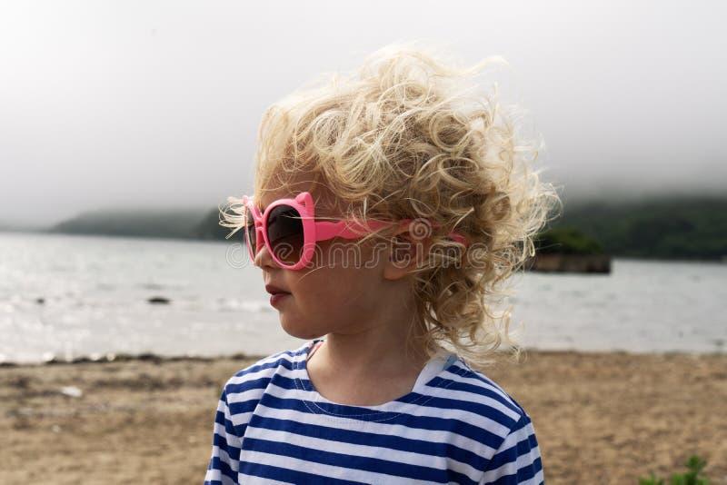 一点背心的卷曲女孩婴孩在太阳镜的海滩站立,并且风翻动她的头发 免版税库存图片