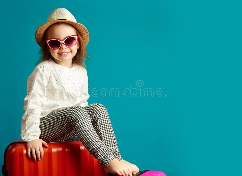 一点草帽和太阳镜的微笑的女孩坐手提箱,继续旅途的漂亮的孩子画象 免版税库存图片