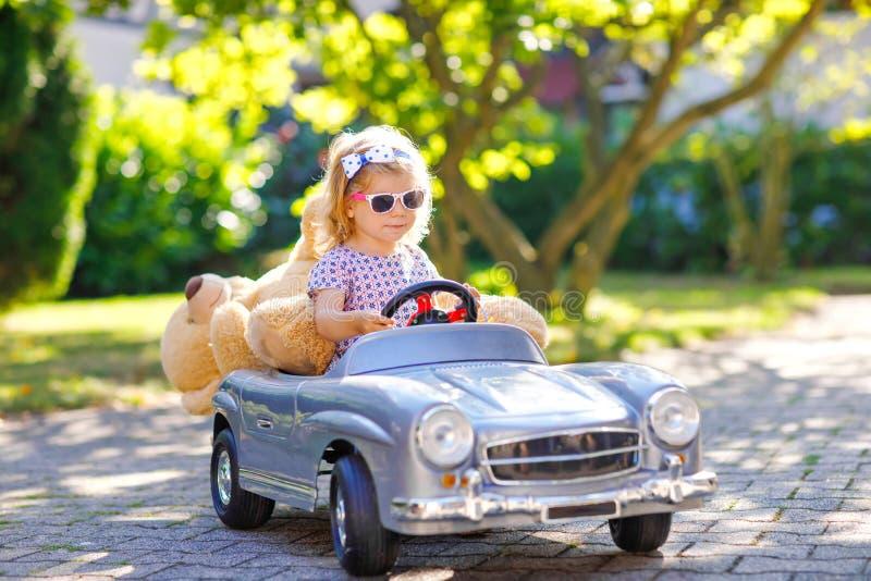 一点获得可爱的小孩的女孩驾驶大葡萄酒玩具汽车和与使用的乐趣与豪华的玩具熊,户外 免版税库存照片