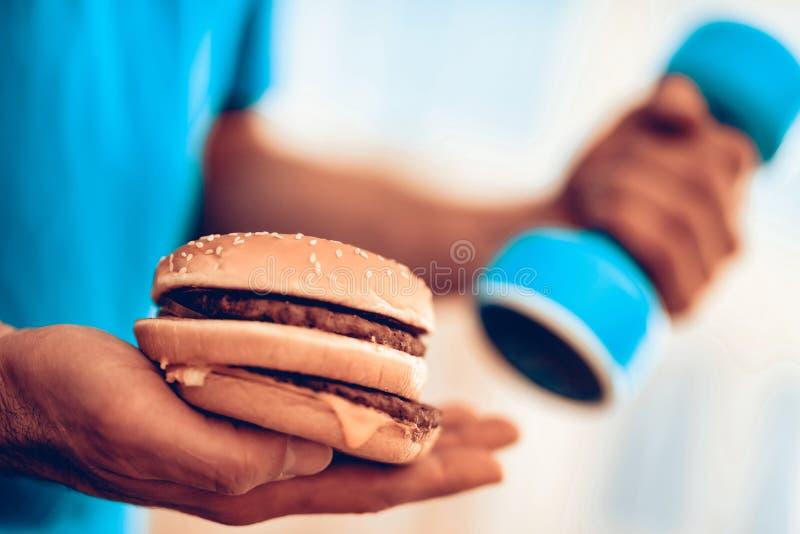 一点蓝色哑铃和大汉堡供以人员手 库存照片