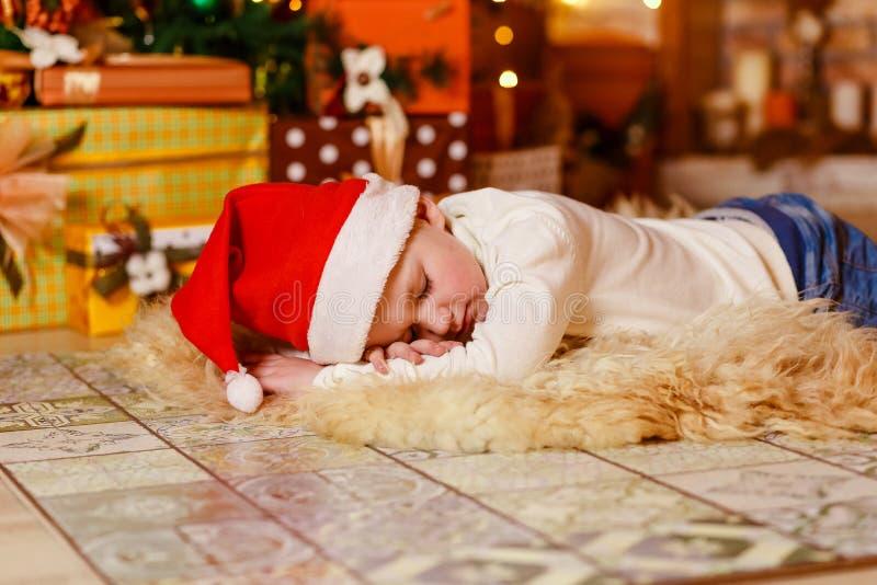 一点说谎在一条蓬松毯子的婴孩在圣诞树下 免版税库存图片