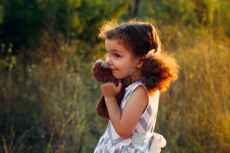 一点逗人喜爱的卷曲女孩hugd一头蓬松玩具猫头鹰 小孩与甜玩偶的女孩戏剧 美好的阳光,温暖的颜色 秋天时间 免版税库存照片