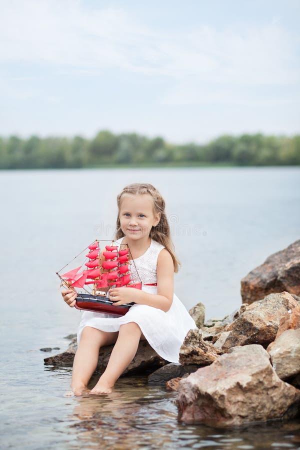 一点逗人喜爱的女孩和猩红色风帆 女孩坐在海滨海洋的岩石有船的 愉快的童年无忧无虑的比赛 免版税库存照片