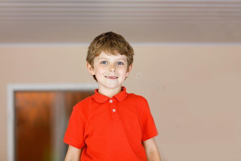 一点逗人喜爱的学校孩子男孩画象以五颜六色的校服时尚穿衣与错过前牙 库存照片