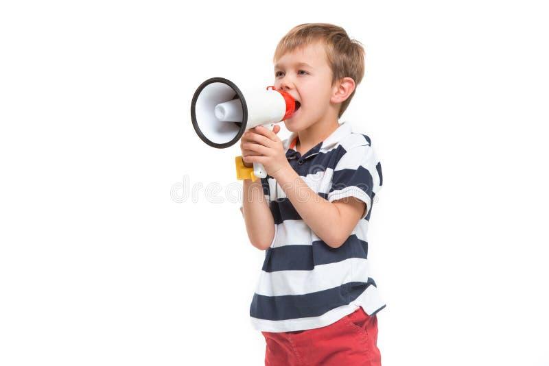 一点逗人喜爱的孩子男婴在手中举行和讲话在电子灰色扩音机 免版税库存照片