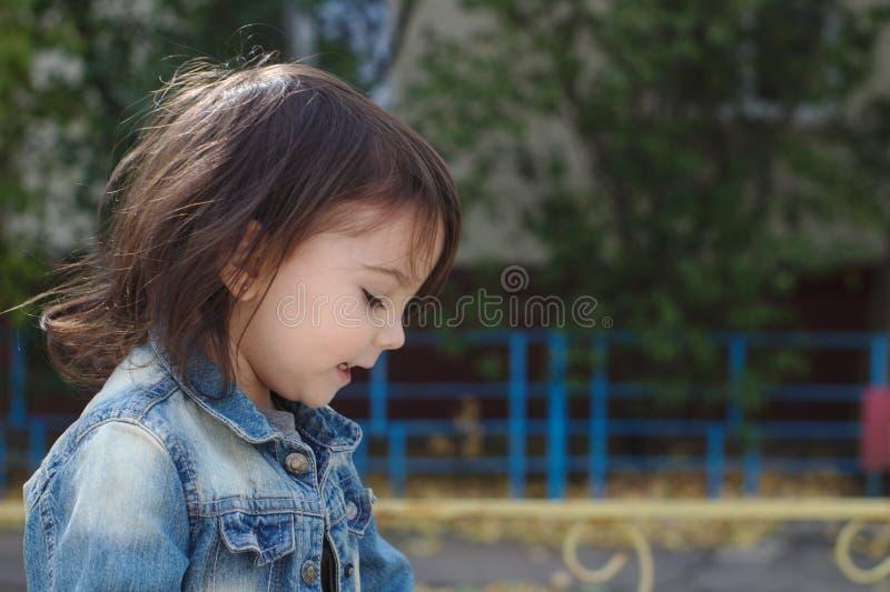 一点逗人喜爱的情感女孩特写镜头画象有猪尾的在牛仔布夹克 免版税库存照片