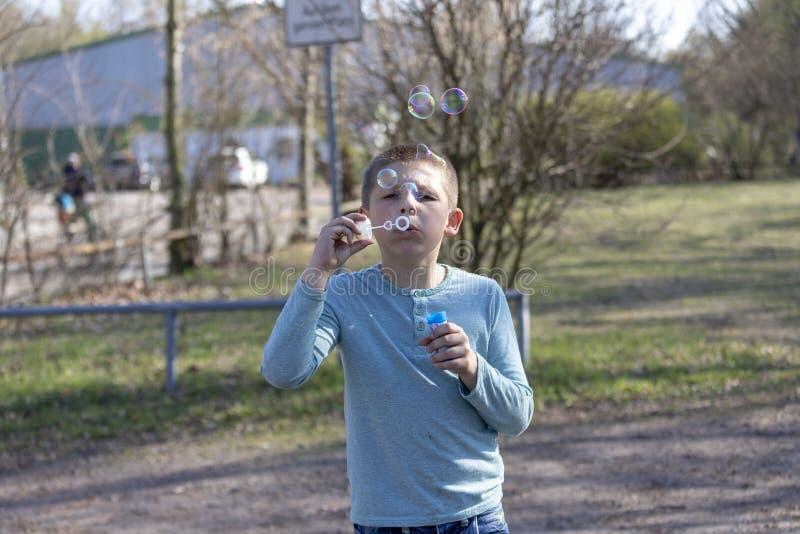 一点逗人喜爱的男孩吹的泡影在公园 免版税库存照片
